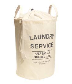 Mörkgrå. En tvättsäck i bomullstwill med texttryck. Överdel i tunnare kvalitet som kan stängas med dragsko. Dubbla handtag upptill. Plastad insida. Storlek