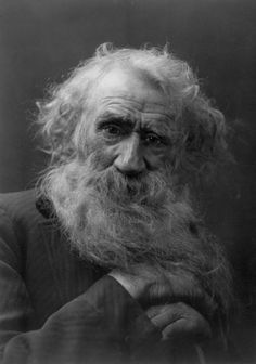 Black and white photograph of a senior caucasian man with scruffy hair and a long beard, resting his hands on a cane, looking forward with his head at a slight tilt as if he is listening to the viewer talk, 1902
