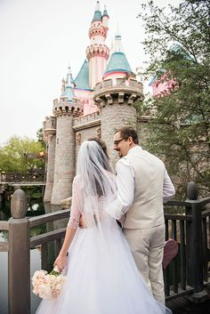 A happy couple in front of Sleeping Beauty Castle.