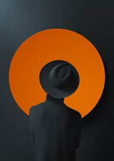 Image Based Design Micah Trower A dark hat-wearing figure, whose suit blends in with the background, surrounded and outlined by a perfect orange circular vector.