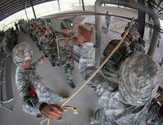 """An Indian Army paratrooper with the 50th Independent Para Brigade hands his static line to a jumpmaster with the U.S. Army, 82nd Airborne Division's 1st Brigade Combat Team in a """"mock door"""" aircraft simulator May 11, 2013, at Fort Bragg, N.C. The paratroopers are preparing for an airborne training exercise as part of Yudh Abhyas, annual training between the Indian Army and United States Army Pacific."""