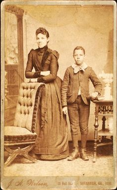 [Unidentified standing figures: woman, her folded arms leaning on back of chair, and young man, probably her son, left hand on book.]