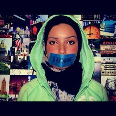 "photograph of empirestateofnoor with tape over her mouth; she is standing against a wall of small photographs and staring into the camera; she is wearing a light green hoodie and a blue and white Hijab; the tape over her mouth has text that reads ""#RIPJUSTICE""    Hoodies N' Hijabs.    Stand up for justice.     Hoodies N' Hijabs."