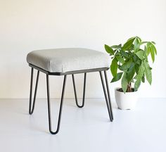 Vintage mid century modern hairpin footstool with a light blue upholstered seat. $50 Etsy