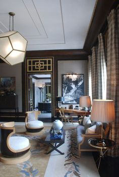jean-louis deniot modern glam living room--black painted moulding, brass accents, grasscloth, klismos slipper chairs, rug