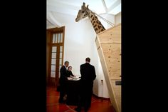 President Barack Obama signs items backstage next to a sculpture of a giraffe in a shipping crate, following remarks at the Palais Des Beaux Arts in Brussels, Belgium, March 26, 2014. With the President are Trip Director Marvin Nicholson and Advance Associate Director Karly Satkowiak. (Official White House Photo by Pete Souza)