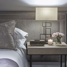Gray bedroom features a long full wall length gray velvet headboard with silver nailhead trim lined with a bed dressed in gray bedding as well as a gray shagreen nightstand.