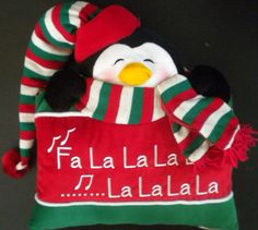 """This cute penguin pillow is the perfect accent for your holiday home.  The pillow measures 16"""" x 18"""" and has a penguin poking his head over a red and green pillow.  The penguin wears a red, white and green striped scarf with red fringe tied around his neck and a red, white and green striped stocking cap with red brim and pom pom.  He also wears black mittens and has a gold-colored beak with eyes closed. Fa La La La La is embroidered in white."""