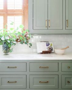 sage green cabinets + marble counters + subway backsplash + brass hardware // classic