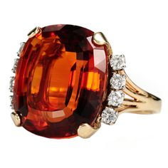 """J. E. CALDWELL  Retro Citrine Diamond  Ring.And luxurious is this 14k gold ring set with a prodigious citrine of an estimated 20.5 carats. Faceted, the citrine is the scintillating color of Madeira wine and just as robust. Claw set in a 14k yellow gold """"throne"""" open work mount, the full-figured gem is bordered on both the east and west with an arch of four (4) brilliant cut diamonds (8 brilliant cuts in all) set in 14k white gold for an estimated total diamond weight of .35 carats. circa…"""