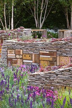 NEW WILD GARDEN DESIGNED BY NIGEL DUNNETT - DRY STONE WALLS WITH INSECT HOUSES.  clivenichols.com