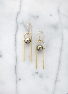 Pyrite spheres are suspended in hammered brass arches. Hypo-allergenic 14k gold filled ear wires. Sterling Silver available. Approx. 2-2.25 long