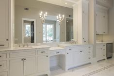 Another view of the master bathroom, showcasing the double sinks with polished nickel hardware and ornate sconces.