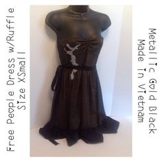 """Free People Black Gold Metallic Strapless Dress Polyester blend.  It has a grey appliqué.  The belt looks better in the back of the dress.  One of the loops for the belt need to be mended. It is still attached, but barely. Approx measurements (flat): Armpit-to-Armpit 12"""".  Length 26"""".  Gently Used in Good Condition.  See labels in picture for additional information. Thank you for stopping by my closet and Happy Poshing! Free People Dresses"""