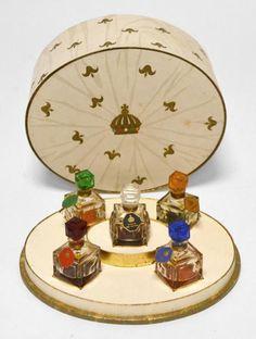 MOLINARD - Les Diamants de la Couronne - (1949) Coffret tambour en carton gainé de papier polychrome illustré de draperies et de fleurs de lys, titré, comprenant cinq flacons d