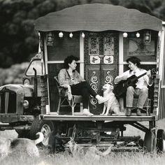 Two Gypsy woman enjoying sitting outside their wagon playing music. jj