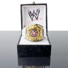 """Officially Licensed WWE R Rated Spinning Championship Belt Replica Finger Ring. Made by Figures Toy Company. The """"R"""" center plate really spins and the ring contains numerous faux diamonds. The ring is made of brass to simulate the gold and also is finished with black hematite to simulate the belt strap. The ring has an adjustable shank that fits rings size 6 to 12 with ease. Ring is shipped in a black jewelry box with the WWE logo printed on the inside of the box."""