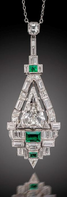 An Art Deco emerald and diamond pendant, of geometric design and set with a central fancy-cut triangular-shaped diamond within a border alternately-set with circular-cut and baguette-shaped diamonds with further triangular-shaped diamonds and emeralds below, in platinum, on fine-link platinum neck chain, pendant 5.2cm long, chain 47cm.