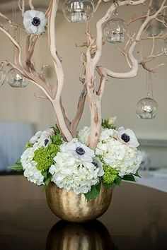 Candlelit glass spheres hang from this ornamental tree, adorned with anemones and hydrangeas. | Photo by Mikkel Paige | Floral design by Flowers by Ivona