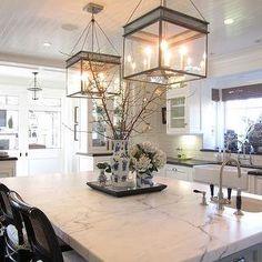 Classic Casual Home - kitchen beadboard ceiling, kitchen island lanterns, calcutta marble countertops, prep sink, cane bar stools, black countertops,farmhouse sink, subway tile,Urban Electric Co.