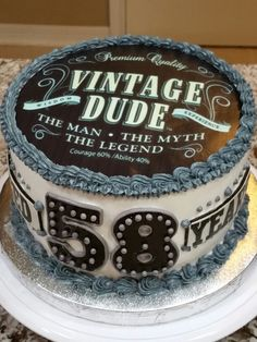 """Popular """"Vintage Dude"""" themed birthday cake. Cake is 8"""" white chocolate w/almond buttercream. Edible icing image on top & """"Aged 58 Years"""" gumpaste accents."""