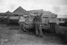 https://flic.kr/p/ntCp79 | Sturmgeschütz 7,5 cm Stu.K. 40 (L/43) Ausf. F (Sd.Kfz. 142/1) Fahrgestell Nr. 91139 | Un Sturmartillerist pose devant sa machine qui semble neuve. D'autres StuGe à canon court sont recouverts d'une tente afin d'en protéger l'habitacle et le canon des intempéries : l'engin est loin d'être étanche ! Courtesy damijwh.blogspot.fr