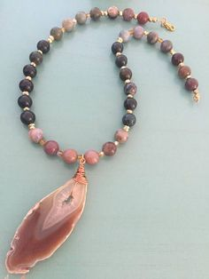 A long, beaded necklace handmade with natural Fancy Jasper in shades of green, mauve and cream, gold Pyrite and amber faceted beads with a wire wrapped agate slice pendant. Necklace Length: Approx. 18 inches This item was handmade by me in my shop in Northern California and will