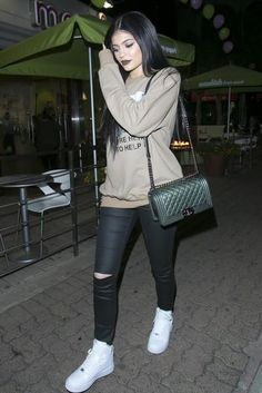 Kylie Jenner wearing Frame Le Skinny Satine Jeans in Vian, Chanel Boy Bag, Fear of God We're Here to Help Crewneck in Camel and Nike Air Force 1 Mid '07 Sneakers