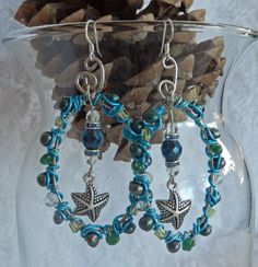 I made these for my ocean loving peeps.    This is a wire wrapped pair of earrings with genuineFreshwater Cultured Pearls, Blue Topaz, Green Aventurine and Peridot gemstones. It's wrapped with colored copper wire.  It has a starfish charm hanging from a faceted bead, blue topaz and rhinestone s...
