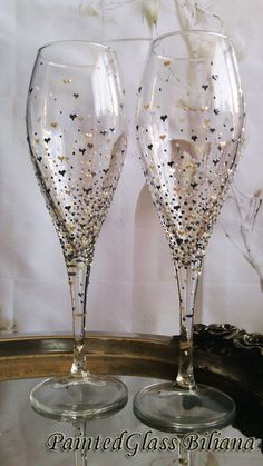 Beautiful set of 2 wine glasses with delicate hand painted hearts and dots in pewter and pearl color.  Hand wash only. The glasses can be