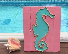 This beachy piece of art is made from reclaimed pallet wood and would be perfect for a nautical inspired beach house! Each sign is hand cut, hand sanded and hand painted. Each sign is made to order so no two will be exactly alike due to variations in the wood. All signs have cable wire on the back for easy hanging. Dimensions are approximately 18 x 15 inches.