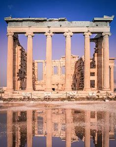 From Athens, Greece to the islands of Milos and Sifnos, a 7 day itinerary with travel tips.  A ruined building with neoclassical columns inside the Acropolis, an ancient green structure.  The structure is reflected in the puddle on the ground.