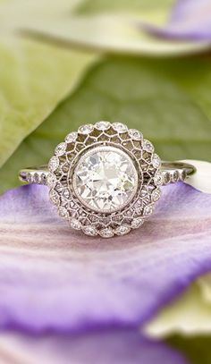 exceptional vintage-inspired ring encircles a bezel set diamond with lavishly detailed latticework and a halo