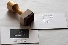 Carpenter rubber stamps business card information onto wooden blocks company stamp designs colourmoves
