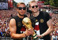 Champions: Gotze and Andre Schurrle celebrate Germany's World Cup win on their return to B...