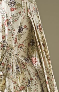 Detail side view, robe à la Française, France, c. 1770. White cotton, block-printed and dye-painted, with silk passementerie.