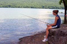 A woman fishes from a large rock at Bald Eagle State Park, Pennsylvania.