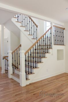 "Natural oak hardwood floor with matching ""Natural"" oak treads paired with alternating double and single box wrought iron spindles and large white newel posts."