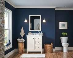 A new vanity adds extra storage and style to your bath. In this room, a white vanity is the perfect contrast to a bold, blue wall.