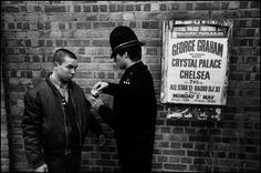 Magnum Photos - Ian Berry GB. ENGLAND. London. Chelsea. Policeman searches a cigarette packet before a Crystal Palace versus Chelsea football match. 1980.