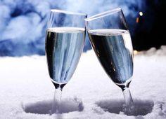 Zwei Gläser Sekt im Schnee, im Hintergrund Silvester Feuerwerk