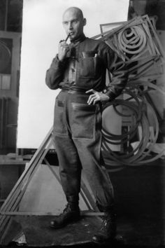 Alexander Rodchenko in the studio dressed in the industrial costume against a background of the spatial constructions. Alexandre Rodtchenko, Aleksandr Rodchenko, Russian Constructivism, The Dark Side, Russian Avant Garde, Russian Art, Dieselpunk, Artist At Work, Wearable Art
