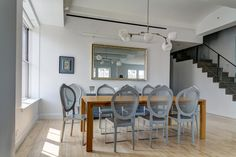 High ceilings and light hardwood flooring help brighten this open design dining area, with a large rich wood table at center hosting a set of grey toned chairs. Asymmetrical chandelier hangs above, reflected in the large gold-framed mirror on the far wall.