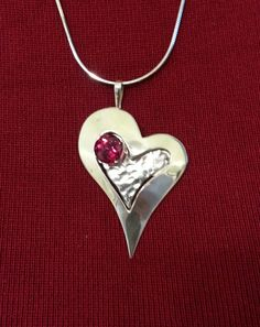 """This heart was made for a very special person. This is a Sterling Silver pendant with a Red Ruby (lab grown) gemstone. It is multi layered with a hammered finish under a highly polished heart. The Ruby is set into the recess space for a depth effect. This is one of many unique designs by """"uniq jewelry""""."""