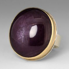 """This Jamie Joseph ring makes a statement with a beautiful, deep purple star ruby. The large, smooth stone is set in a 14k yellow gold bezel on Jamie's sterling silver 'Comfort Z' band. This casual ring makes it easy to incorporate precious gems into your everyday attire! <br><br>Stone measures approximately 1"""" x 7/8"""" <br><br>Size 6.5<br><br><div><b>"""