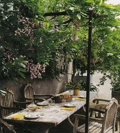 Outdoor dining with wood table and chairs lush greenery canopy, image from Axel Vervoordt's Timeless Interiors