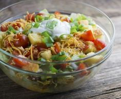Cornbread, spicy ground beef, cheese and veggies come together for this easy, pretty layered taco salad!
