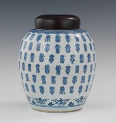 "A Chinese Blue and White Thousand Longevity Symbol Design Jar, Possibly Early Qing Of globular form decorated throughout with a ""Thousand Longevity"" symbols, all painted in slightly different form, all within ruyi and scroll borders; unglazed neck and a newer carved wood lid; wax-resist base, underside marked with underglaze blue concentric circles, and has a partial red wax export seal. 10""H x 8""W."