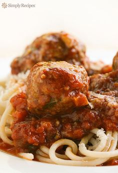 It's time for Spaghetti and Meatballs! Classic Italian American spaghetti pasta with tomato-based sauce with mushrooms, basil, Parmesan with herb-seasoned meatballs made with ground beef and Italian sausage. So amazingly good!! On SimplyRecipes.com