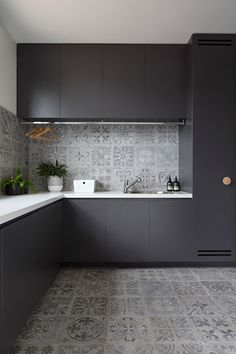 In this modern laundry room, matte black cabinets provide a strong contrast to the light grey tiles and the white countertops. A drying bar has been installed to hang drying clothes, and a sink makes clean-up or soaking clothes easy.